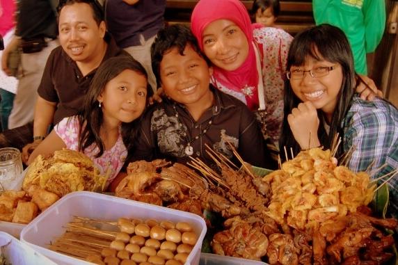 Indonezyjska rodzina zasiada do ulicznej uczty